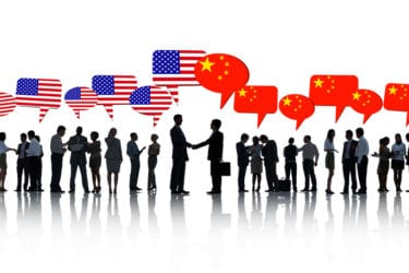 American And Chinese Business Men Shaking Hands Amongst The Rest Of The Business People